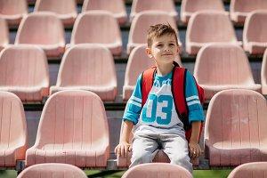 Schoolboy sitting at a stadium