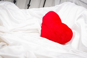 Heart-shaped Pillow On White Sheets