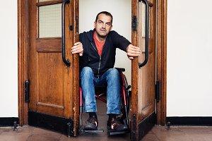 Man In Wheelchair Having Trouble Going Through Door