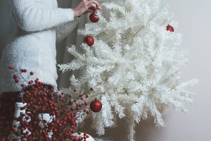 Closeup photo of young woman decorating white Christmas Tree at home,