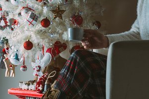 Woman sitting next to the Christmas tree with a coffee in her hand