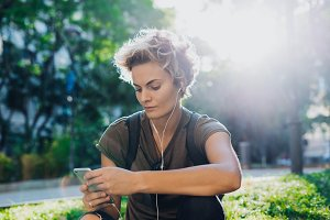 Young woman listening music on phone