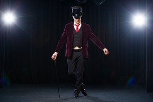 Magician, Juggler man, Funny person, Black magic, Illusion standing on the stage with a cane of beautiful light