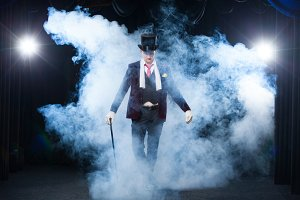Magician, Juggler man, Funny person, Black magic, Illusion standing on the stage with a cane of beautiful light. shrouded in a beautiful mysterious smoke