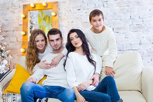 happy family with two children boy and girl sitting on couch in light blouses and blue jeans. Christmas.