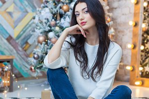 Christmas. Beautiful smiling girl. is sitting over christmas tree lights background. happy new year.