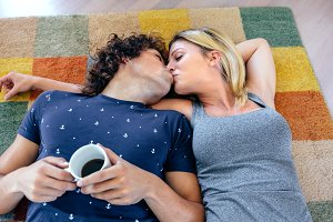 Couple kissing lying on the carpet