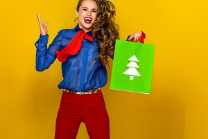 smiling modern woman with Christmas shopping bag jumping