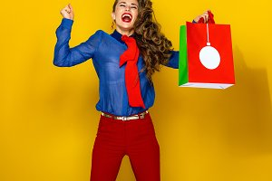 smiling woman with Christmas shopping bag rejoicing and jumping