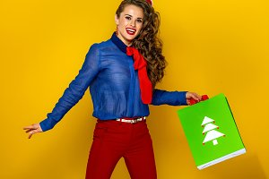 woman on yellow background with Christmas shopping bag jumping