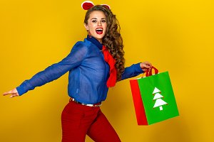 smiling modern woman with Christmas shopping bag running