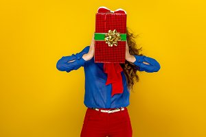 woman holding red present box in the front of her face