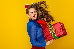 woman isolated on yellow background with red present box running