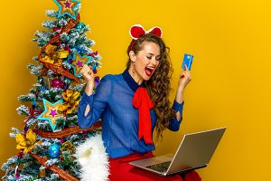 woman near Christmas tree with laptop and credit card rejoicing