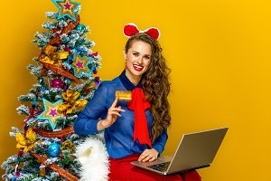 woman near Christmas tree with laptop showing credit card
