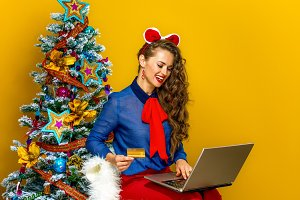 woman near Christmas tree making online purchases on a laptop