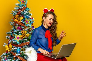 smiling woman near Christmas tree having video chat on laptop