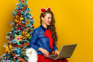 woman near Christmas tree on yellow background using laptop