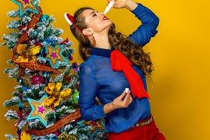 trendy woman near Christmas tree using nasal spray