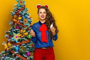smiling modern woman near Christmas tree holding nasal spray