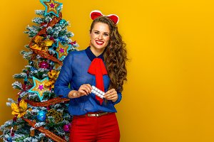 happy young woman near Christmas tree holding pack of pills