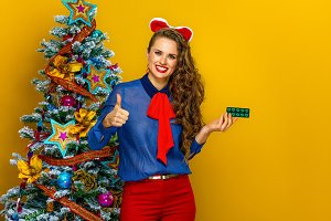 woman near Christmas tree showing thumbs up and pack of pills