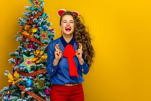 smiling trendy woman near Christmas tree with crossed fingers