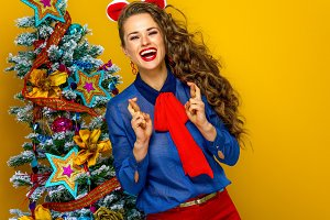 happy trendy woman near Christmas tree with crossed fingers