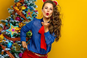 smiling young woman near Christmas tree blowing air kiss