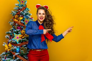 happy stylish woman near Christmas tree pointing at something