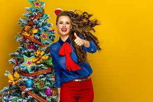 happy trendy woman near Christmas tree showing thumbs up