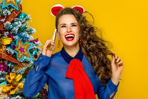 happy woman near Christmas tree talking on a mobile phone
