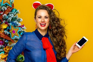 smiling woman near Christmas tree showing phone blank screen