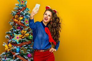 woman near Christmas tree with digital camera taking selfie