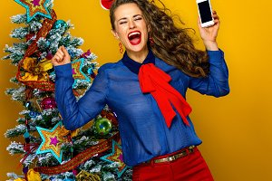 happy woman near Christmas tree with smartphone rejoicing