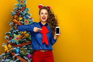 woman near Christmas tree pointing at cellphone blank screen