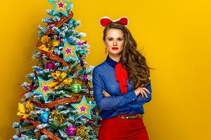 modern woman standing near Christmas tree on yellow background