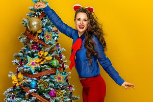 happy elegant woman hanging Christmas ball on a tree