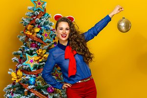 smiling stylish woman showing Christmas ball