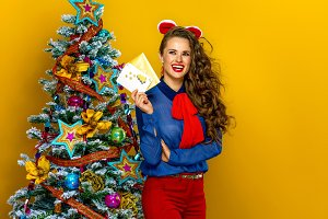 smiling woman near Christmas tree with envelope and postcard