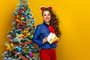 happy young woman near Christmas tree with envelope and postcard