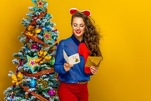 happy woman near Christmas tree with envelope reading postcard