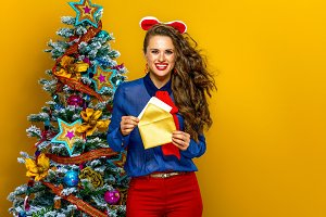 happy woman near Christmas tree holding envelope and postcard