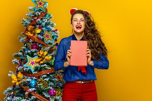 smiling trendy woman near Christmas tree woman holding a book