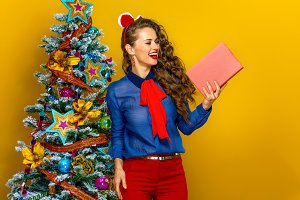 happy trendy woman near Christmas tree looking at book