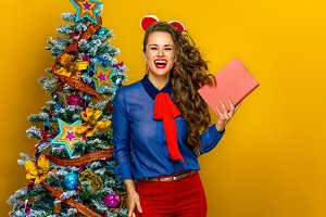 happy stylish woman near Christmas tree showing a book