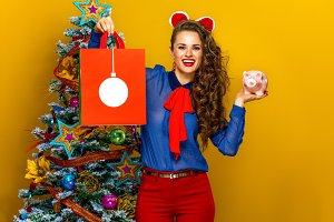 smiling woman showing Christmas shopping bag and piggy bank
