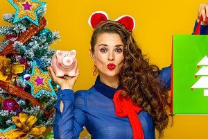 cheerful woman showing Christmas shopping bag and piggy bank