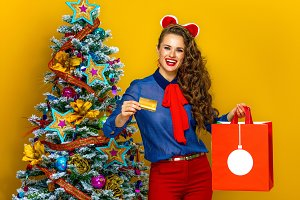 smiling woman with Christmas shopping bag showing credit card