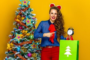 woman with Christmas shopping bag pointing at alarm clock